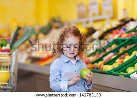 Cute little girl reading checklist while holding apple at grocery store
