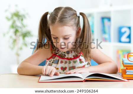 Cute little girl reading story from big book in the nursery room