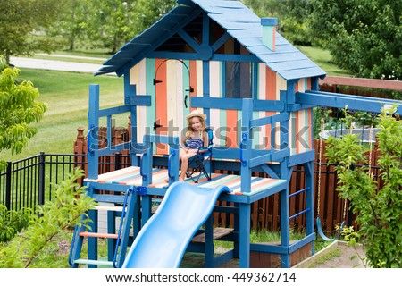 Cute little girl relaxing in foldable chair on private outdoor recreation playground with ladder, slide, door and window