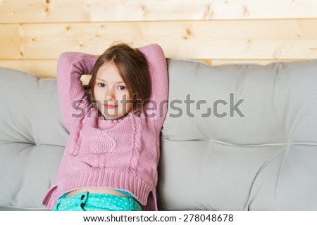 Cute little girl resting on a terrace, sitting on a sofa - stock photo