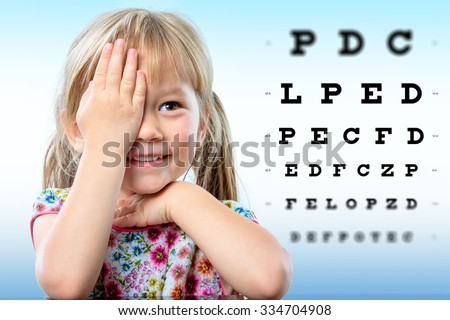 Cute little girl reviewing eyesight.Girl closing one eye with hand reading block letters on vision chart with focus point. - stock photo
