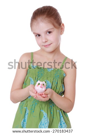 Cute little girl saving money in a piggy-bank, isolated on white