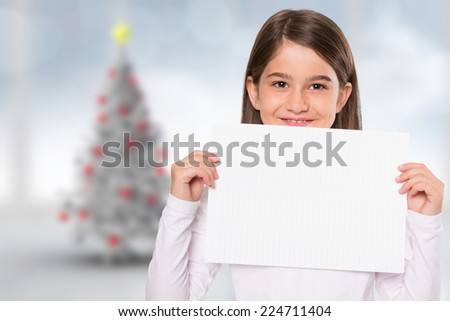 Cute little girl showing card against blurry christmas tree in room - stock photo