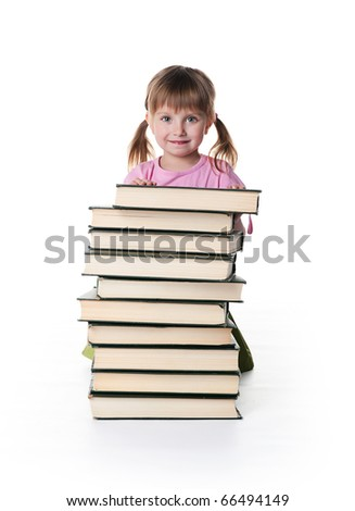 Cute little girl sit near a stack of big books on white background