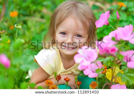 Cute little girl sitting among the flowers. Sunny summer day - stock photo