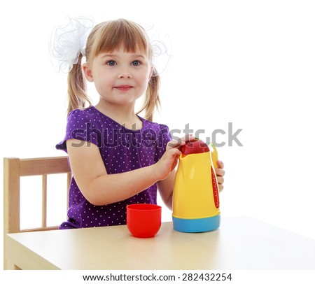 Cute little girl sitting at a table and holding a toy coffee pot- isolated on white background