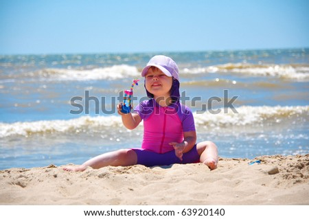 Cute little girl sitting at the seashore