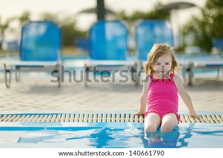 Cute little girl sitting by a swimming pool - stock photo