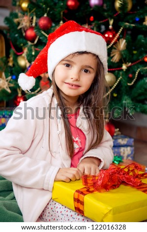Cute little girl sitting in front of christmas tree - stock photo