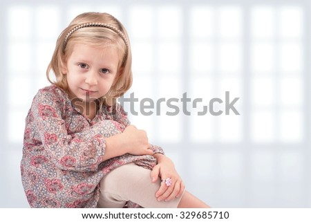 Cute little girl sitting in front of windows - stock photo