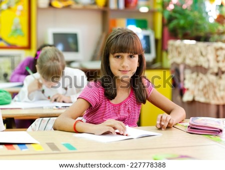 Cute little girl sitting in the classroom and smiling. Elementary age. Other kids in the background.