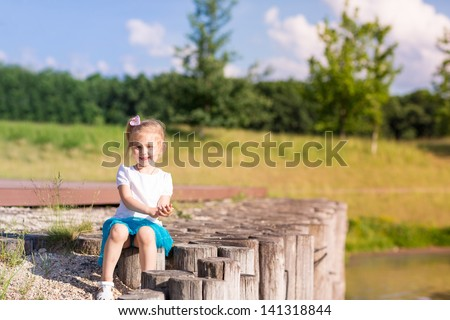 Cute little girl sitting near the lake in summertime in nature