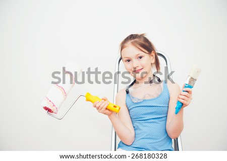 Cute little girl sitting on a step ladder, holding a roller and a brush - stock photo