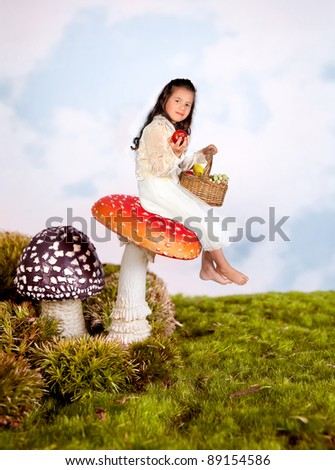 Cute little girl sitting on a toadstool in a fairytale - stock photo