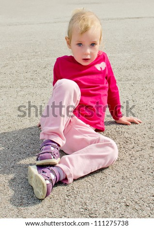 Cute little girl sitting on asphalt
