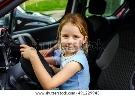 Cute little girl sitting on driver place in a car, childhood