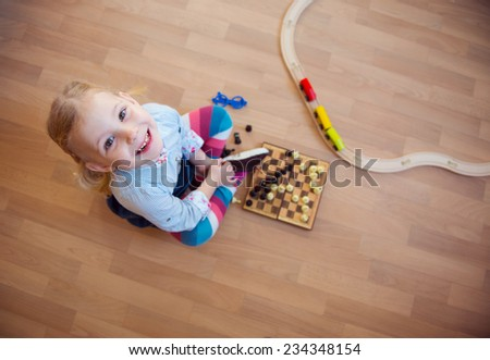 Cute little girl sitting on floor and playing chess - stock photo