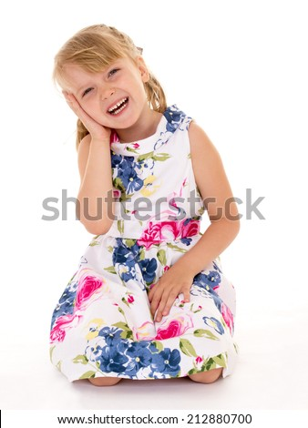 Cute little girl sitting on her lap on a white background.The concept of a child's learning and development. - stock photo