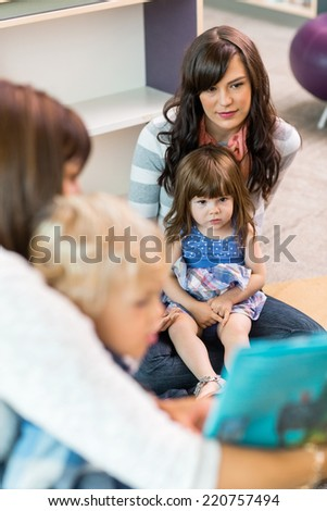 Cute little girl sitting on teacher's lap in school library - stock photo