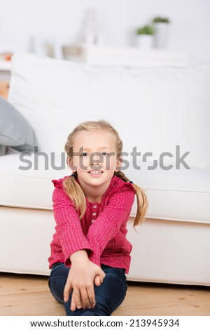 cute little girl sitting on the floor in the living room at home - stock photo