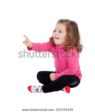 Cute little girl sitting on the floor pointing something with the finger isolated on a white background - stock photo