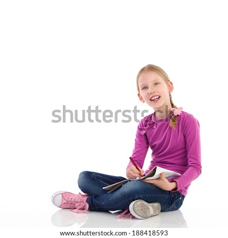 Cute little girl sitting on the floor with crossed legs, drawing and looking away. Full length studio shot isolated on white.