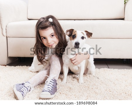 Cute little girl sitting on the floor with her dog - stock photo