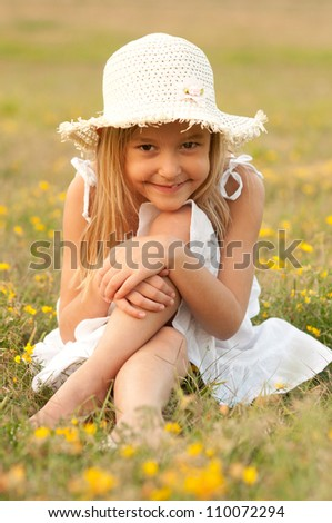 Cute little girl sitting on the meadow on sunny summer day. - stock photo