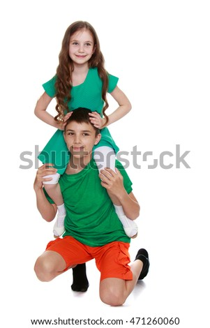 Cute little girl sitting on the neck of his brother - Isolated on white background