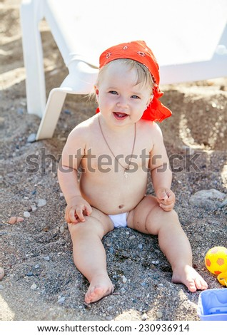 Cute little girl sitting on the sand and plays