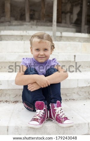 Cute little girl sitting on the stone
