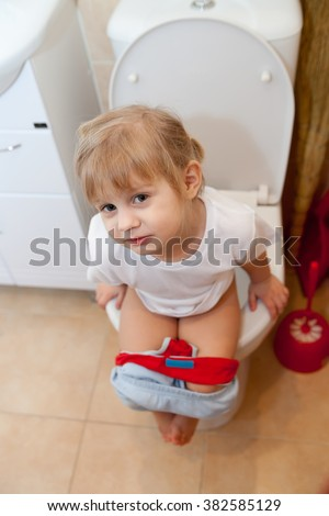 Little Girl Is Sitting On Toilet Royalty Free Stock