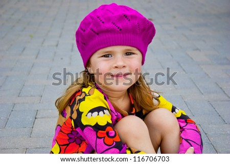 Cute little girl sitting outside wearing colorful clothes