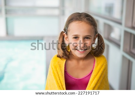 Cute little girl sitting poolside at the leisure center