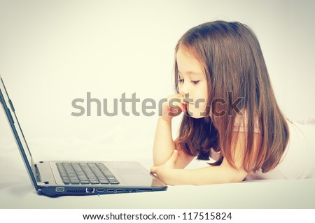 Cute little girl sitting with a laptop