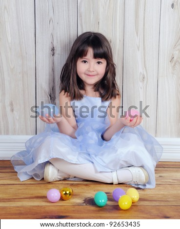 cute little girl sitting with easter eggs in hands - stock photo