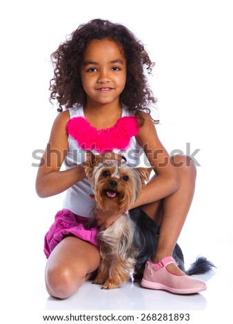 Cute little girl sitting with his puppy Yorkshire terrier smiling at camera on white background