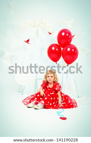 Cute little girl sitting with red balloons in a white room surrounded with paper birds. - stock photo