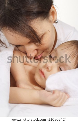 Cute little girl sleeping in bed at home with mom
