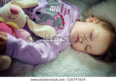 Cute little girl sleeping with a toy