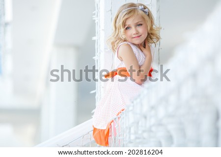 cute little girl smiling in the city. Beautiful blonde girl outside in a field with sunlight on her hair. - stock photo
