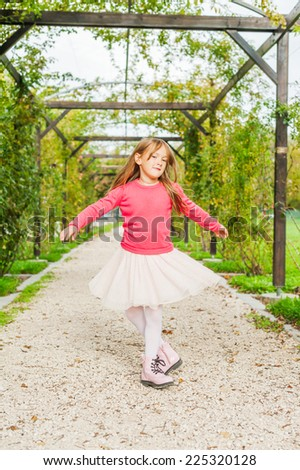 Cute little girl spinning around in a beautiful park, wearing tutu skirt, pink pullover and boots - stock photo