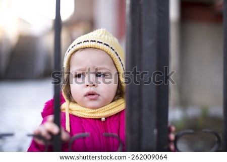 cute little girl standing in front of a gate in winter - stock photo