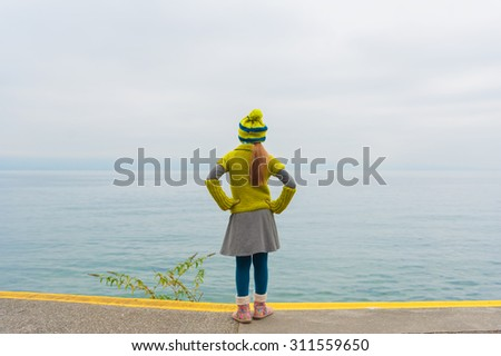 Cute little girl standing next to beautiful lake on a cold day, back view, wearing warm knit pullover and hat, boots - stock photo