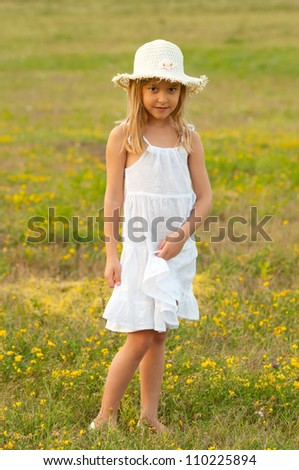 Cute little girl standing on the meadow on sunny summer day. - stock photo