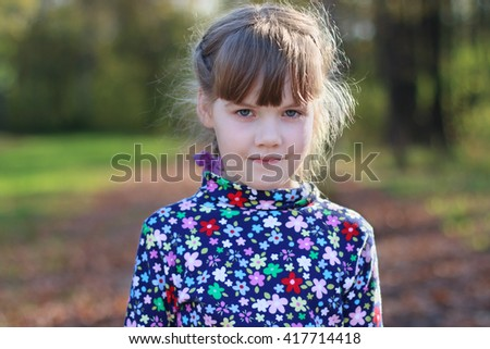 Cute little girl stands in sunny green park, shallow dof, close up - stock photo