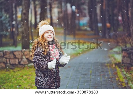 Cute little girl stretches her hand to catch falling snowflakes. Toning instagram filter.