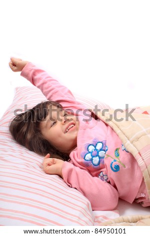 Cute little girl stretching her arms happily with a smile from waking up in her bed. - stock photo