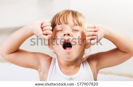 Cute little girl stretching in bed. - stock photo
