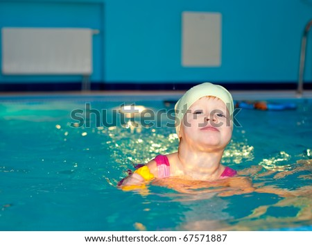 Cute little girl swimming in a pool - stock photo